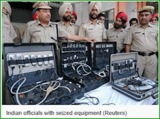 Indian police officials seizing gambling related equipments